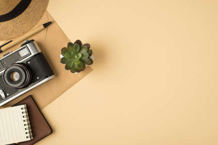 Top view photo of cap plant pen notebook passport cover and camera on craft paper envelope on isolated beige background with copyspace 免版税图像