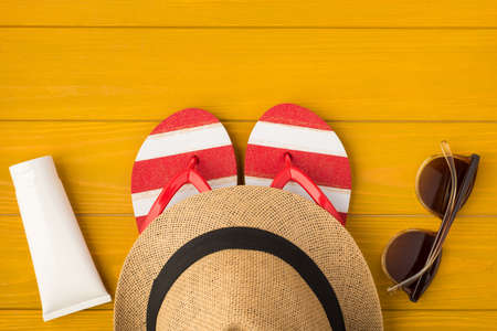 Above photo of headwear sunhat flip-flops sunglasses and sunscreen isolated on the yellow wooden background 免版税图像
