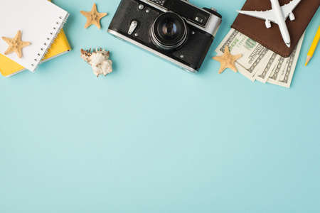 Top view photo of yellow notebooks camera pencil plane model on passport cover with dollars seashell and starfishes on isolated pastel blue background with copyspace