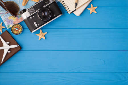 Overhead photo of camera starfish notepad pen sunglasses map plane and compass isolated on the blue wooden background with blank space 免版税图像