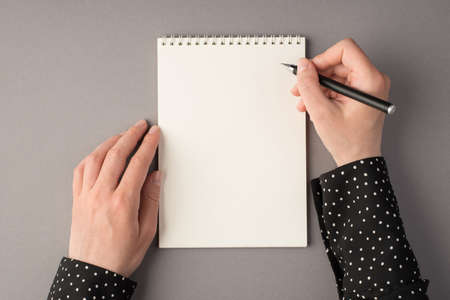 First person top view photo of woman's hands holding pen open copybook on isolated gray background with blank space
