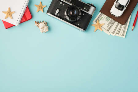 Top view photo of red copybooks camera pencil car model on passport cover with dollars seashell and starfishes on isolated pastel blue background with copyspace 免版税图像