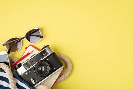 Above photo of sunglasses phone bag camera notebook and pencil isolated on the yellow background with empty space