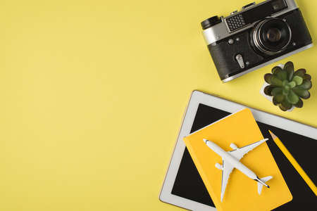 Top view photo of camera flowerpot tablet computer pencil and plane model on yellow planner on isolated pastel yellow background with copyspace 免版税图像
