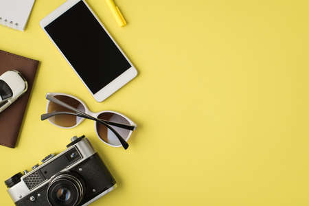 Top view photo of smartphone display notebook pen sunglasses camera and plane model on passport cover on isolated pastel yellow background with copyspace 免版税图像