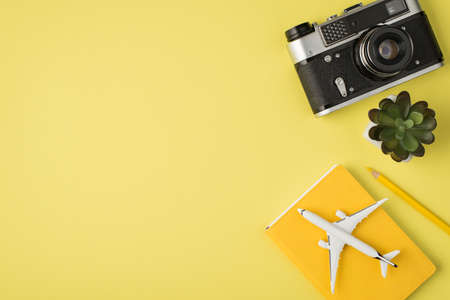 Top view photo of camera plant pencil and plane model on planner on isolated pastel yellow background with copyspace 免版税图像