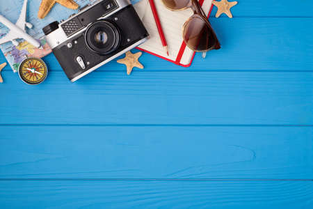 Overhead photo of camera starfish notepad pencil sunglasses map plane and compass isolated on the blue wooden background with blank space