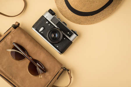 Top view photo of sunhat camera and sunglasses on leather bag on isolated beige background