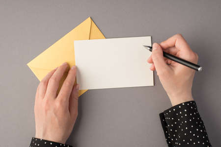 First person top view photo of female hands holding pen over white card closed pastel yellow envelope on isolated gray background with blank space 免版税图像