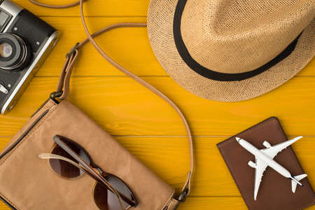 Above photo of sunhat camera bag sunglasses passport and airplane isolated on the yellow wooden background