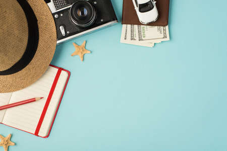 Top view photo of cap camera red pencil planner starfishes and car model on passport cover with dollars on isolated pastel blue background with copyspace