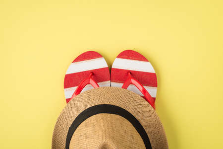 Top view photo of striped red and white flip-flops and sunhat on isolated pastel yellow background with copyspace