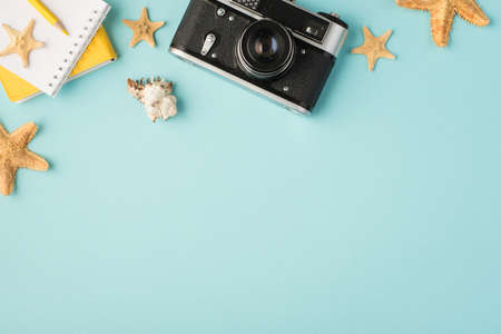 Top view photo of yellow notebooks pencil camera seashell starfishes and camera on isolated pastel blue background with copyspace 免版税图像