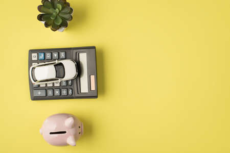 Top view photo of flowerpot car model on calculator and piggy bank on isolated pastel yellow background with copyspace