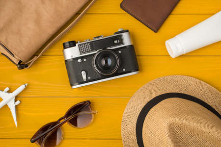 Above photo of sunhat camera bag sunglasses passport sunblock and airplane isolated on the yellow wooden background 免版税图像