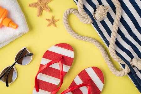 Top view photo of white towel orange sunscreen bottle starfishes beach bag striped flip-flops and sunglasses on isolated pastel yellow background