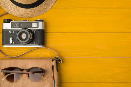 Overhead photo of camera sunhat leather bag and sunglasses isolated on the yellow wooden background with copyspace