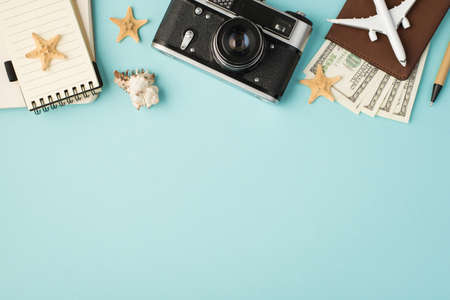 Top view photo of notebooks camera pen plane model on passport cover with dollars seashell and starfishes on isolated pastel blue background with blank space 免版税图像