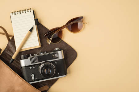 Top view photo of open leather bag with copybook pen sunglasses and camera on isolated beige background with copyspace