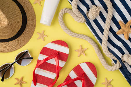 Top view photo of sunhat cream bottle beach bag striped flip-flops sunglasses and starfishes on isolated pastel yellow background 免版税图像