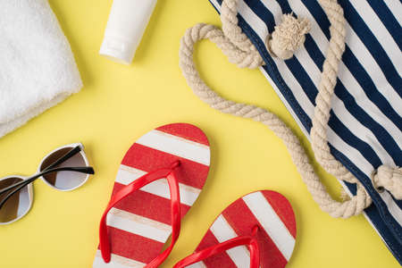Top view photo of white towel cream bottle beach bag striped flip-flops and sunglasses on isolated pastel yellow background