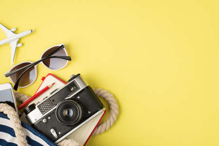 Overhead photo of sunglasses phone bag camera notebook pencil and plane isolated on the yellow background with copyspace 免版税图像