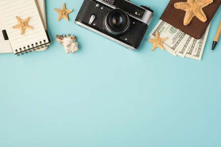 Top view photo of notebooks camera pen passport cover with dollars seashell and starfishes on isolated pastel blue background with copyspace