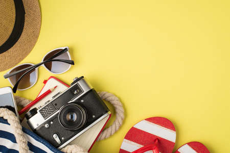 Above photo of hat sunglasses phone bag camera notebook pencil and sandals isolated on the yellow background with blank space