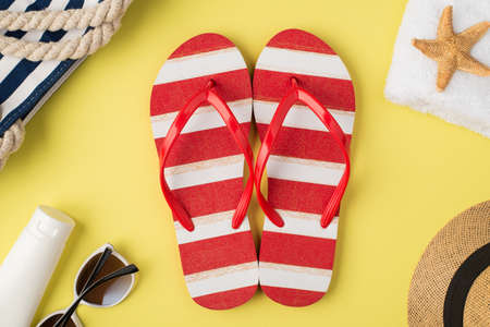 Top view photo of beach bag towel starfish hat cream bottle sunglasses striped red and white flip-flops on isolated pastel yellow background,