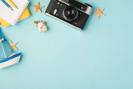 Top view photo of notebooks pencils camera ship toy seashell starfishes and camera on isolated pastel blue background with copyspace 免版税图像