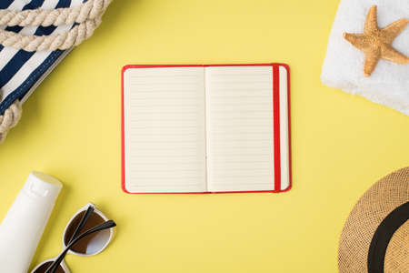 Top view photo of beach bag white towel cream bottle sunglasses cap starfish and open red planner in the middle on isolated pastel yellow background with blank space