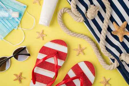 Top view photo of sanitizer medical masks cream bottle beach bag striped flip-flops sunglasses and starfishes on isolated pastel yellow background