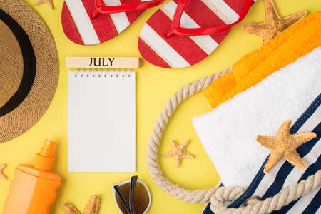 Top view photo of notebook with inscription july starfishes beach bag with orange and white towels sunscreen bottle cap sunglasses and flip-flops on isolated yellow background with blank space