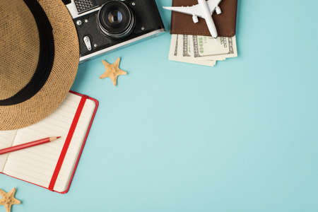 Top view photo of sunhat camera red pencil planner starfishes and plane model on passport cover with dollars on isolated pastel blue background with copyspace