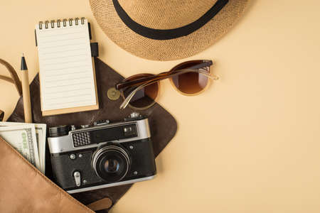 Top view photo of open leather bag with copybook pen camera money sunglasses and headwear on isolated beige background with copyspace