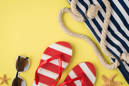 Top view photo of beach bag striped red and white flip-flops sunglasses and starfishes on isolated pastel yellow background with copyspace