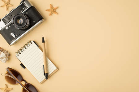 Top view photo of camera planner pen sunglasses seashell and starfishes on isolated beige background with blank space