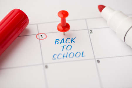 Closeup photo of mark on calendar at first blue inscription back to school with red pushpin and marker