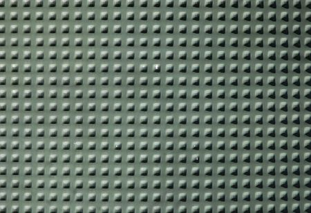 perforated: Green textured wall with square perforated knobs