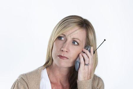distraught: A distraught mature blond female talking on a cellular phone Stock Photo