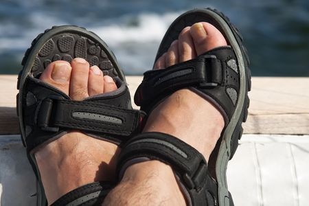 hairy legs: A pair of male feet on the stern of a boat with ocean in the background