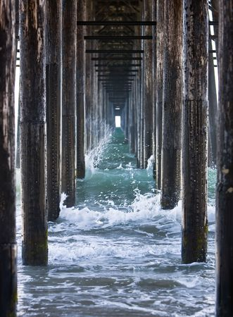 crashing: Waves crashing underneath a pier while the tide is rolling out. Stock Photo