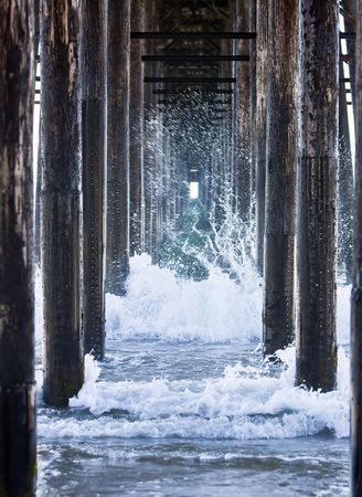 Waves crashing underneath a pier while the tide is rolling out. photo