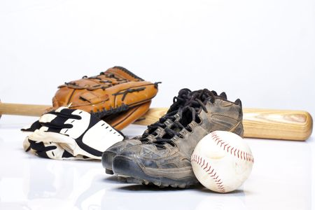 cleats: Used baseball cleats against a glove, softball, bat, and batting gloves on a white background