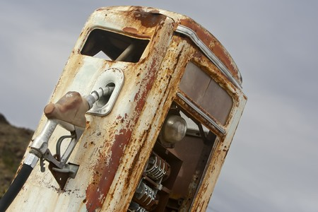 A vintage rusted gas pump abandoned in the desert photo