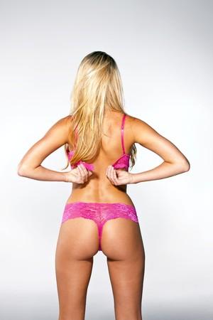 blonde close up: Blonde model adjust bra strap in a studio environment Stock Photo