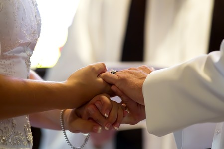 A young couple hold hands as they take their wedding vows