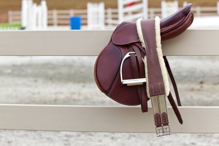 light brown horse: A dark english saddle sits on a fence with jumps in the background
