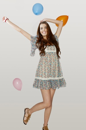 A young brunette model poses with colorful balloons photo