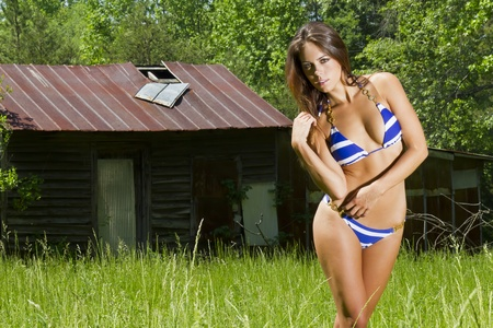 A brunette model posing in an outdoor environment wearing a striped blue bikini Stock Photo - 10000372